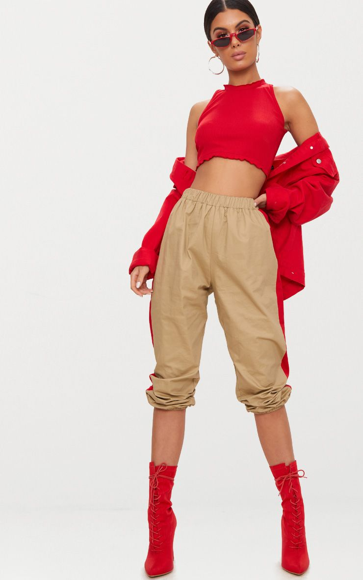 Mannequin wearing a red crop top, beige pants and red boots